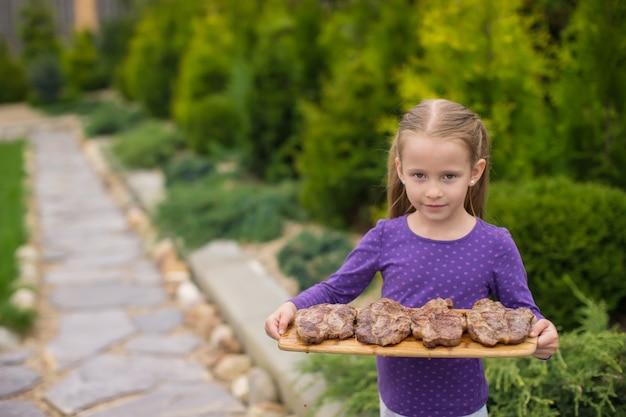 Adorable niña con filetes a la parrilla en las manos al aire libre