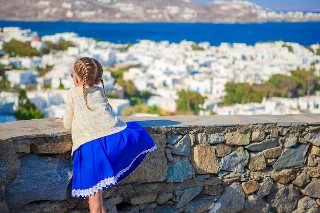 Adorable niña en el fondo de la ciudad de mykonos increíble vista de casas blancas tradicionales