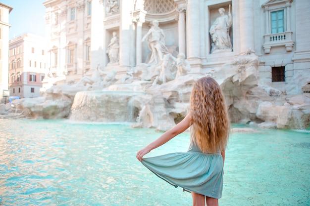 Adorable niña en la fontana de trevi, roma, italia.