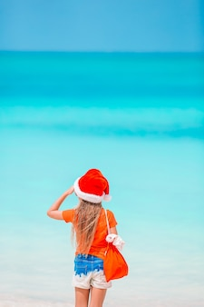 Adorable niña con gorro de papá noel con una bolsa de regalos en la playa tropical