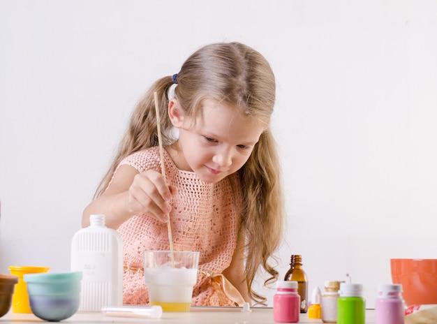 Adorable niña haciendo juguete de limo, combina ingredientes para un juguete hecho a sí mismo popular en todo el mundo.