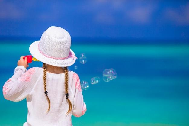 Adorable niña haciendo pompas de jabón durante las vacaciones de verano