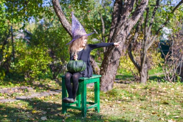 Adorable niña en halloween cuyo disfraz se divierte al aire libre