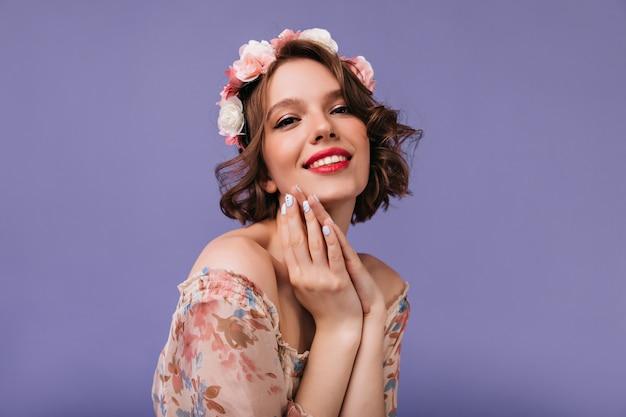 Adorable niña con hermosas flores en el cabello posando. mujer blanca inspirada con sincera sonrisa de pie.