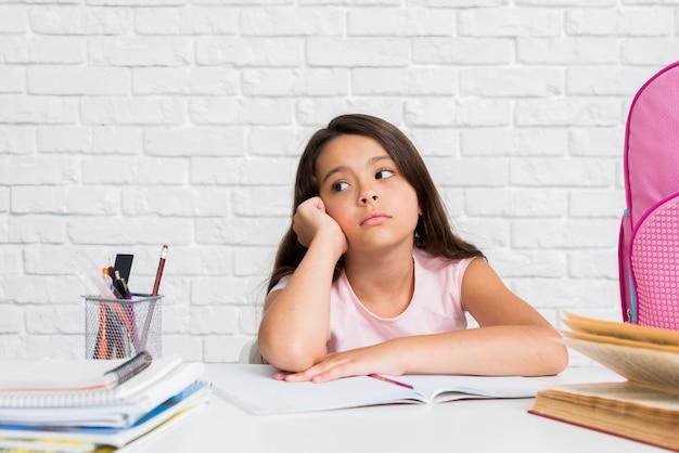 Adorable niña hispana aburrida haciendo la tarea