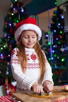 Adorable niña horneando galletas de jengibre para navidad