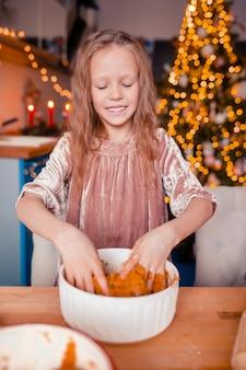 Adorable niña horneando galletas de jengibre de navidad