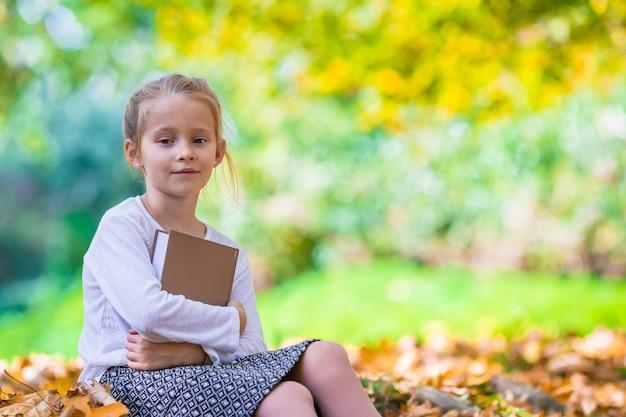 Adorable niña inteligente con libro en otoño hermoso dau al aire libre