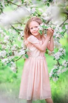 Adorable niña en jardín floreciente cerezo al aire libre