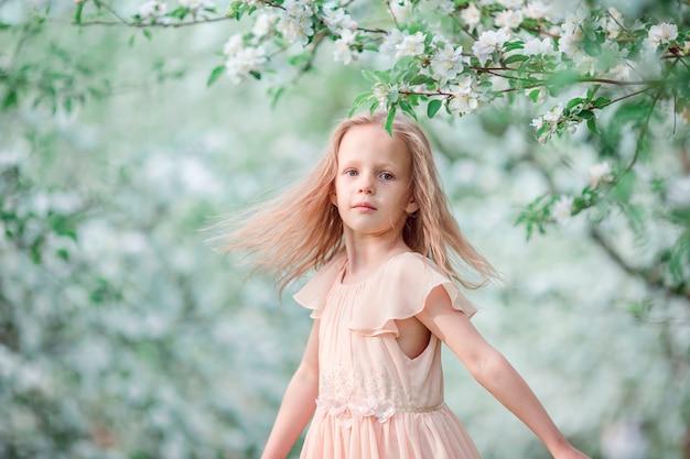 Adorable niña en jardín floreciente de cerezo en primavera