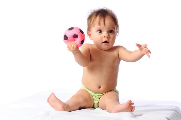 Adorable niña juega con una pequeña pelota de fútbol rosa