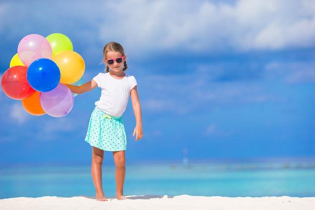 Adorable niña jugando con globos en la playa