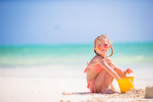 Adorable niña jugando con juguetes de playa en la playa blanca
