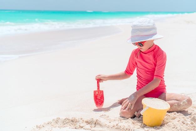 Adorable niña jugando con juguetes de playa durante vacaciones tropicales
