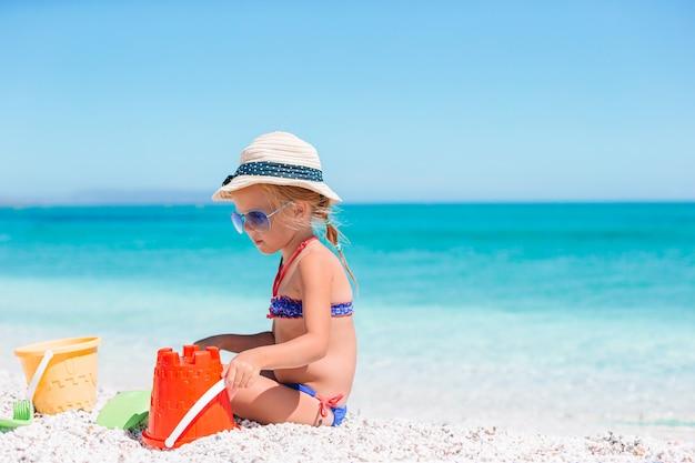 Adorable niña jugando en la playa con arena