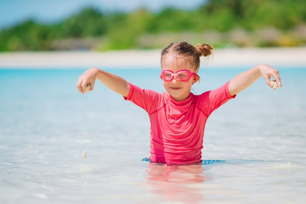 Adorable niña jugando en la playa con pelota