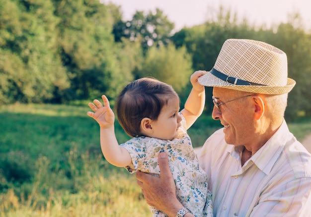 Adorable niña jugando con el sombrero de hombre mayor sobre un fondo de naturaleza. concepto de dos generaciones diferentes.