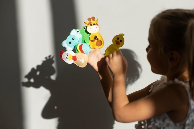 Adorable niña jugando con sus títeres en casa