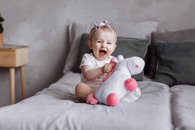 Adorable niña está jugando con unicornio de juguete en la cama en su casa. concepto del día de la infancia. feliz bebé, día de la familia