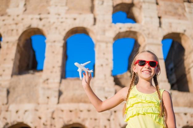 Adorable niña con juguete pequeño modelo avión fondo coliseo en roma, italia