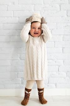 Adorable niña levantando su sombrero