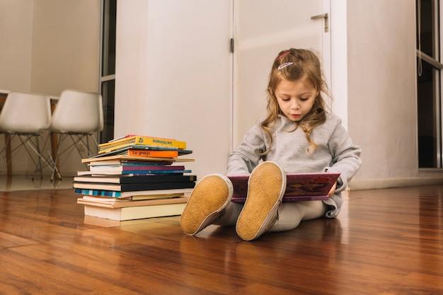 Adorable niña leyendo libros en el piso