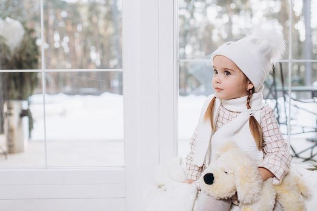 Adorable niña linda en sombrero de punto en el interior en casa. navidad, vacaciones de invierno, concepto de infancia