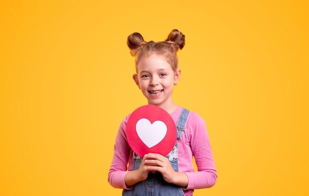 Adorable niña con lindos bollos de pelo sonriendo y mostrando el signo del corazón