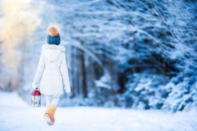 Adorable niña con linterna en invierno en navidad al aire libre