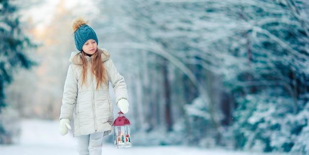 Adorable niña con linterna y vela en invierno