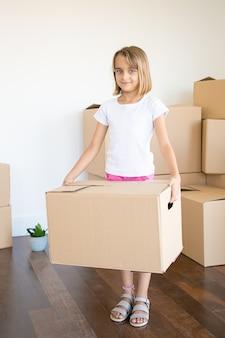 Adorable niña llevando caja de cartón y mirando a cámara
