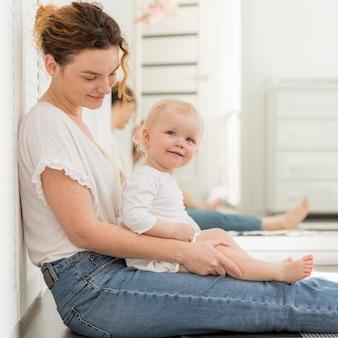 Adorable niña con madre en casa