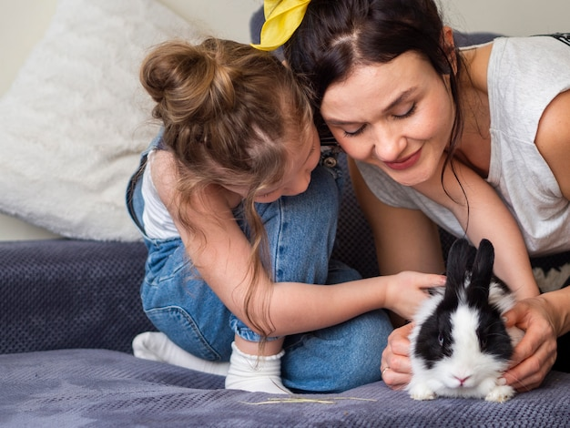 Adorable niña y madre jugando con conejo