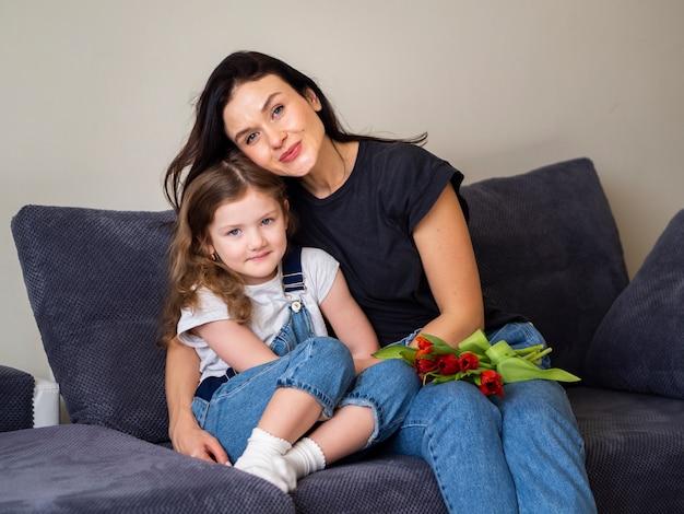 Adorable niña y madre posando juntos