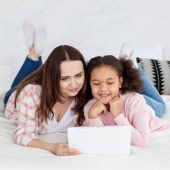 Adorable niña mirando dibujos animados con madre