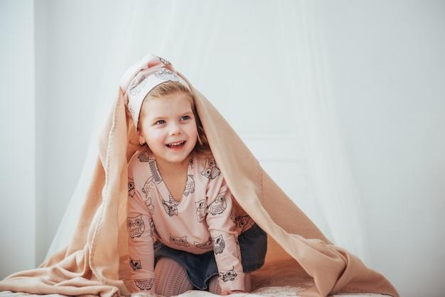 Adorable niña, mirando bajo una toalla