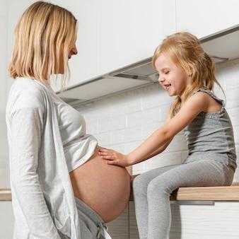Adorable niña mirando el vientre de la madre
