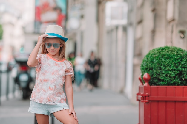 Adorable niña de moda al aire libre en ciudad europea