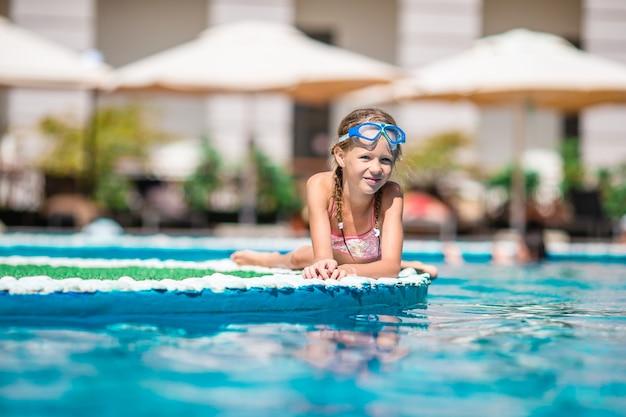 Adorable niña nadando en la piscina al aire libre