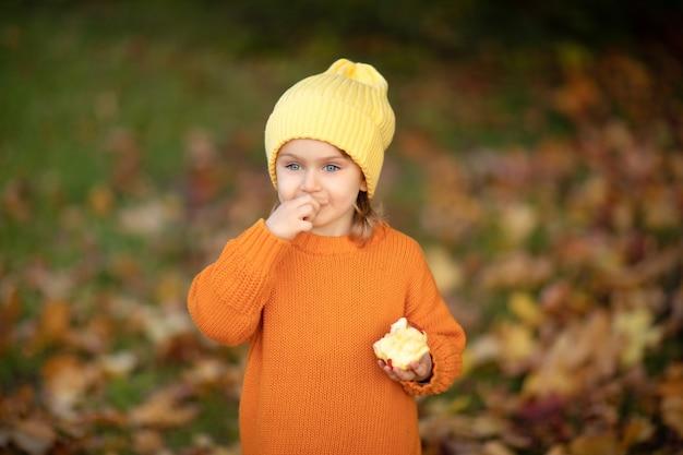 Adorable niña niño con gorro de punto amarillo y suéter naranja en el fondo de la naturaleza