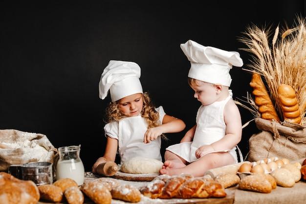 Adorable niña con niño en la mesa de cocina