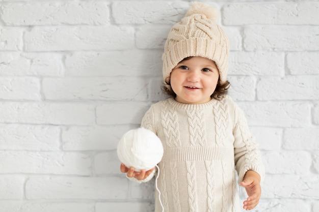 Adorable niña ofreciendo una bola de nieve