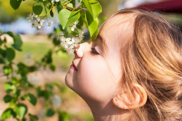 Adorable niña oliendo flores de cerca