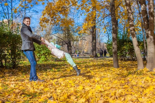 Adorable niña con papá feliz divirtiéndose en el parque otoño en un día soleado