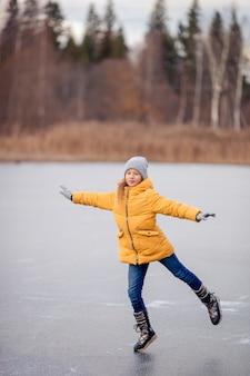 Adorable niña patinando en la pista de hielo