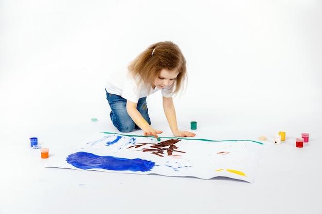 Adorable niña, peinado moderno, camisa blanca, jeans azules dibuja imágenes de sus manos con pinturas. aislar.