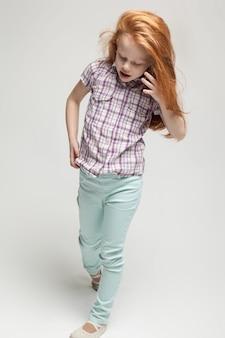 Adorable niña pelirroja linda con camisa a cuadros, pantalones azules brillantes y botas blancas