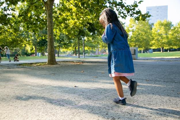 Adorable niña de pelo negro jugando a la rayuela en el parque de la ciudad. longitud total, espacio de copia. concepto de infancia