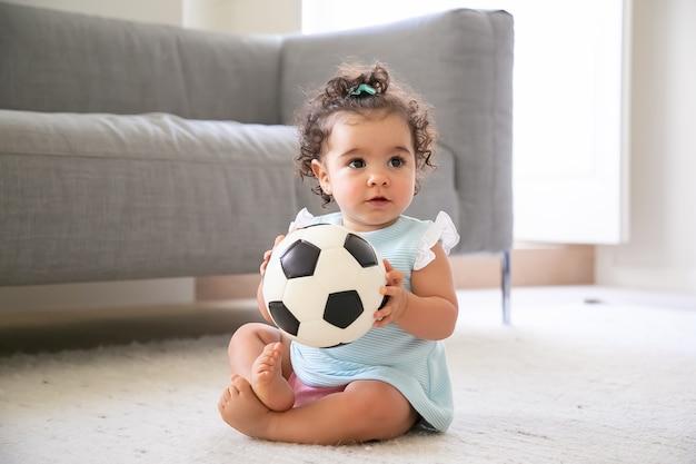 Adorable niña de pelo negro con ropa azul pálido sentada en el suelo en casa, mirando a otro lado, jugando al fútbol. niño en casa y concepto de infancia.