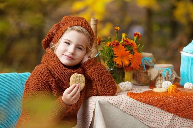 Adorable niña en un picnic en el parque otoño